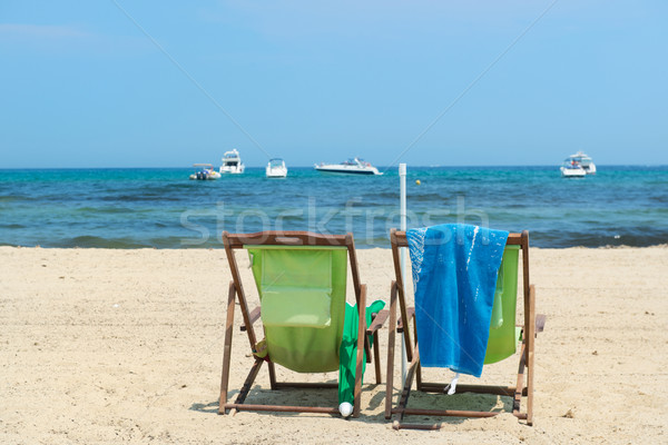 Beach with green chairs and boats in water Stock photo © ivonnewierink