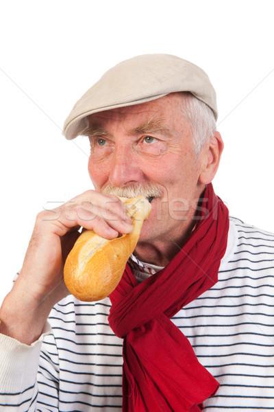 Idős férfi eszik francia kenyér portré sapka Stock fotó © ivonnewierink