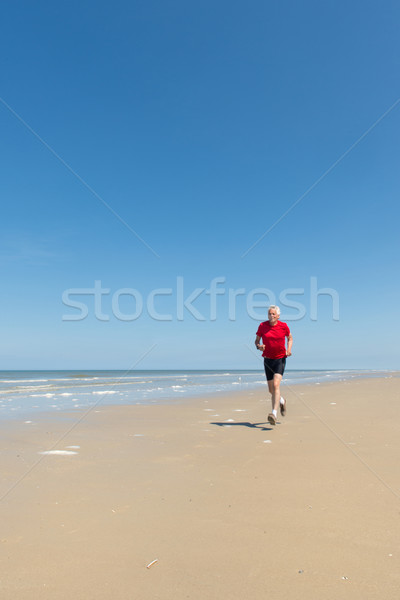 Elder man running at the beach Stock photo © ivonnewierink
