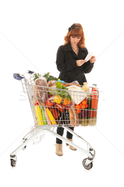 Woman with full shopping cart reading shopping list Stock photo © ivonnewierink