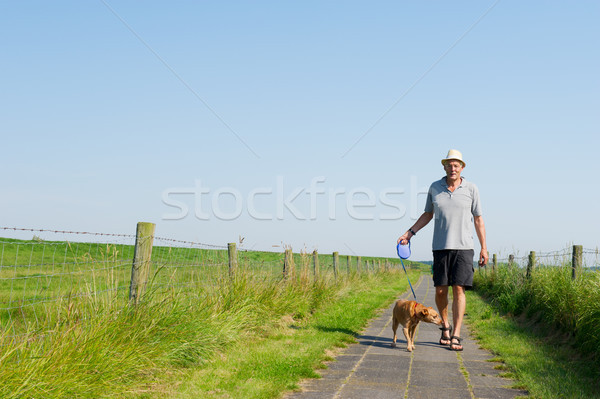 Elderly man walking the dog Stock photo © ivonnewierink