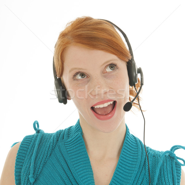 Young red haired woman with head set looking surprised Stock photo © ivonnewierink