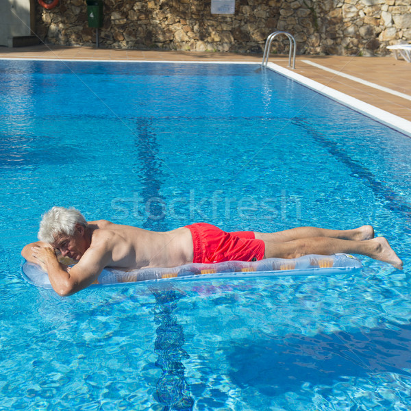 Senior man floating on water Stock photo © ivonnewierink