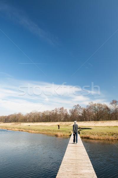 Man walking away over water Stock photo © ivonnewierink