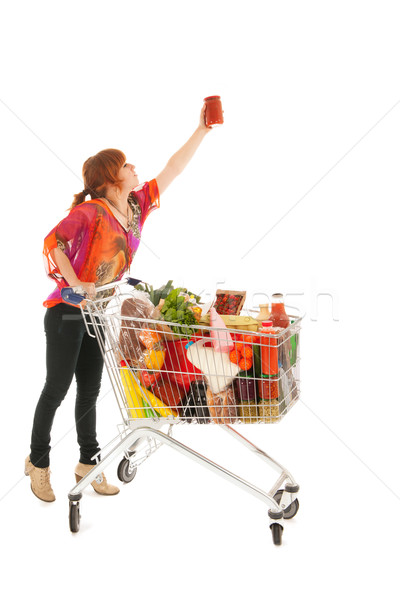 Woman with Shopping cart picking food from high cupboard Stock photo © ivonnewierink