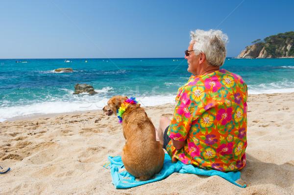 Senior man with dog on beach Stock photo © ivonnewierink