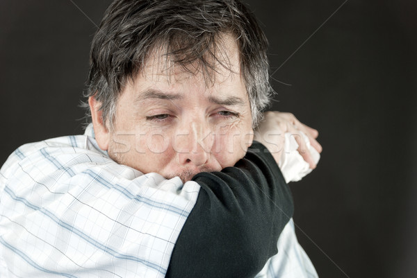 Man Stifles Sneeze In Elbow Stock photo © jackethead