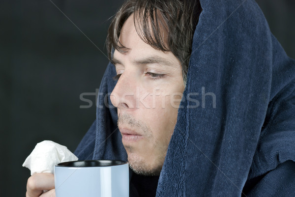 Sick Man Blowing On Hot Mug Stock photo © jackethead