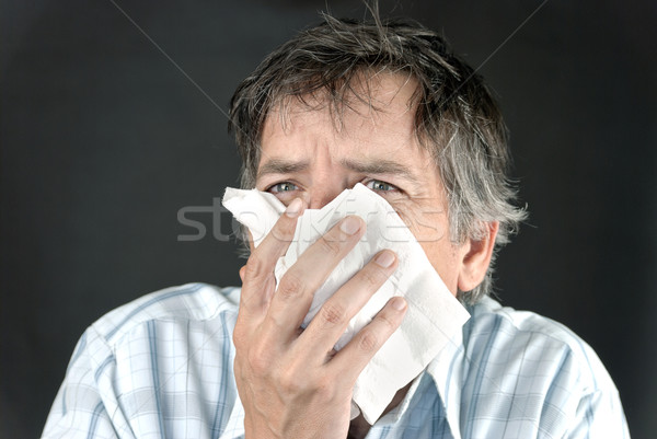 Man Sneezing Into Tissue Stock photo © jackethead