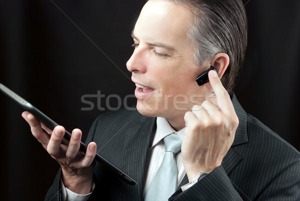 Businessman Using Tablet Adjusting Headset Earpiece. Stock photo © jackethead