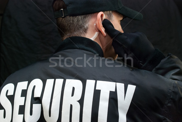 Stock photo: Security Guard Listens To Earpiece, Back of Jacket Showing
