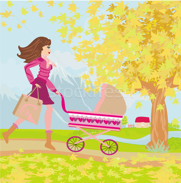 Young mom taking her baby for a stroll through park in autumn Stock photo © JackyBrown