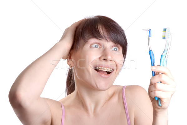 Woman with braces with toothbrushes Stock photo © jagston
