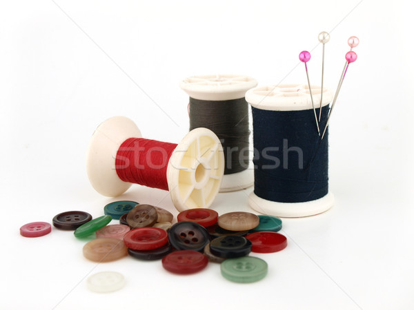a spool of thread, needle and button Stock photo © jakgree_inkliang