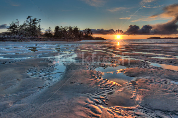 Sunstar Sunset with Colorful Beach Foreground Stock photo © jameswheeler