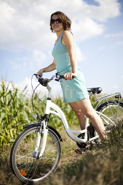 Stock photo: Young woman riding a bicycle