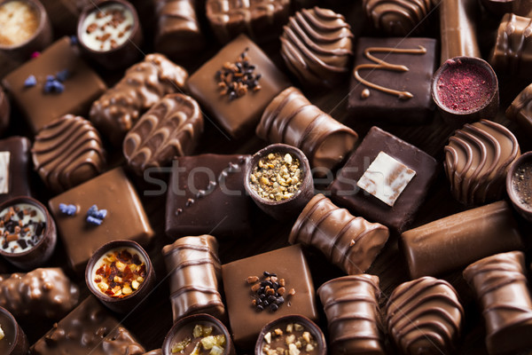 Chocolate bars and pralines on wooden background Stock photo © JanPietruszka