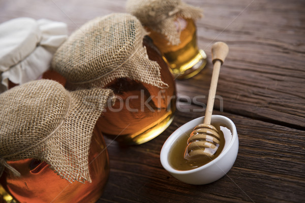 Honey jar with dipper and flowing honey Stock photo © JanPietruszka