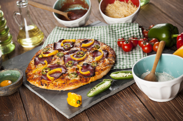 Tasty pizza, tomatoes and others ingredients on a wooden backgro Stock photo © JanPietruszka