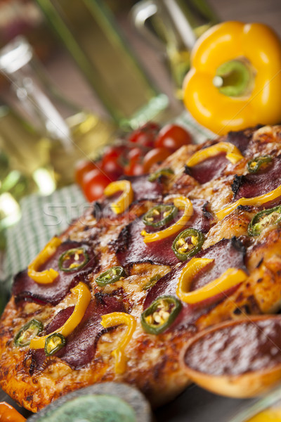 Stock photo: Tasty pizza, tomatoes and others ingredients on a wooden backgro