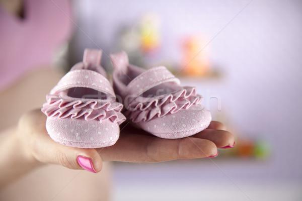 Pregnant woman holding a pair of tiny shoes Stock photo © JanPietruszka