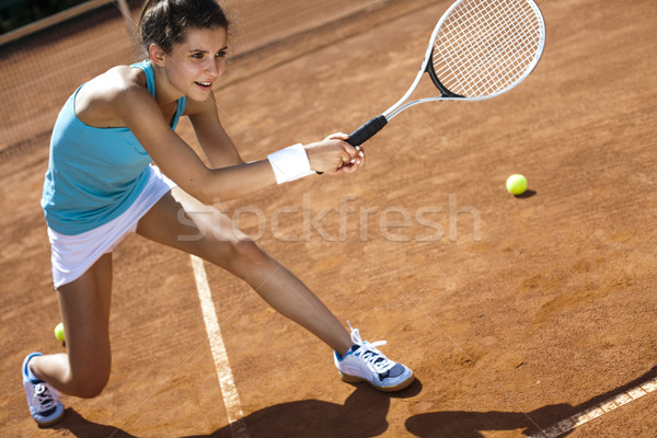 Stock photo: Young woman tennis player on the court