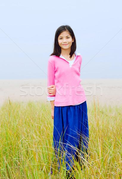 Girl standing in tall grassy field Stock photo © jarenwicklund