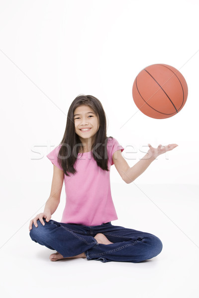 Stock photo: Ten year old Asian girl holding basketball, isolated on white