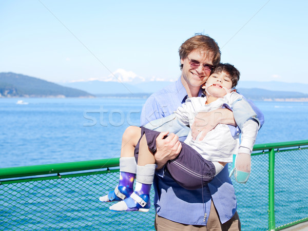 Father holding disabled son in arms on deck of ferry boat. Stock photo © jarenwicklund