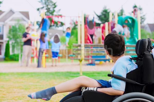 Disabled little boy in wheelchair watching children play on play Stock photo © jarenwicklund