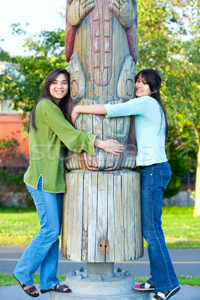 Two young, biracial teen girl in park hugging a totem pole on su Stock photo © jarenwicklund