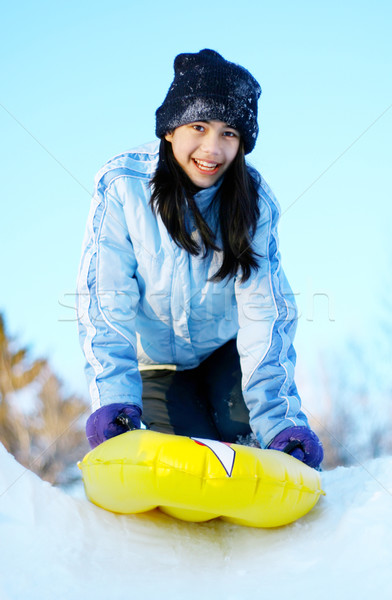 Biracial teen girl sledding down snow hill Stock photo © jarenwicklund