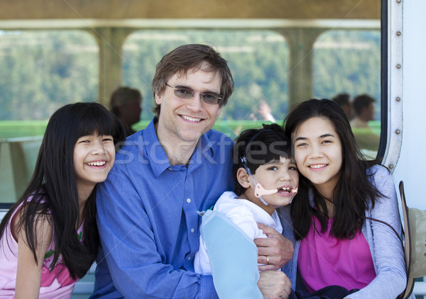 Father with his biracial children, holding disabled son on ferry Stock photo © jarenwicklund