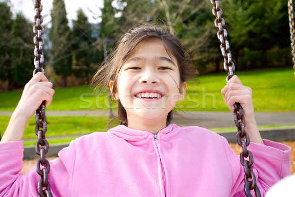 Happy little girl smiling on a swing at the park Stock photo © jarenwicklund