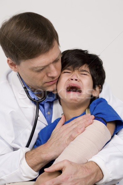 Male doctor comforting scared  toddler patient. Child is disabled with cerebral palsy. Stock photo © jarenwicklund
