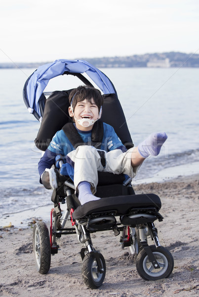 Happy disabled boy in wheelchair on the beach Stock photo © jarenwicklund
