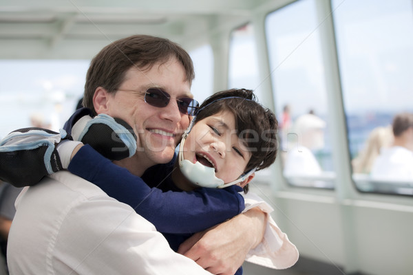 Stock photo: Father hugging disabled son as they ride a ferry boat