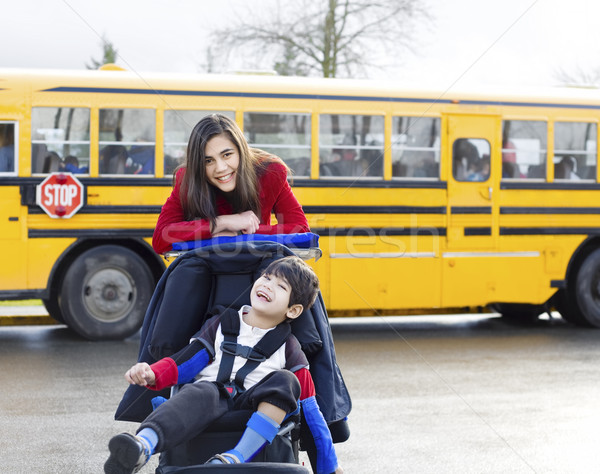 Big sister with disabled brother in wheelchair by school bus Stock photo © jarenwicklund
