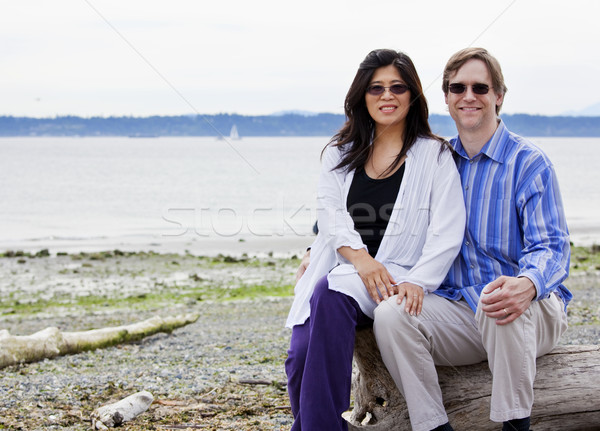 Interracial couple in forties together on beach, sitting on log Stock photo © jarenwicklund