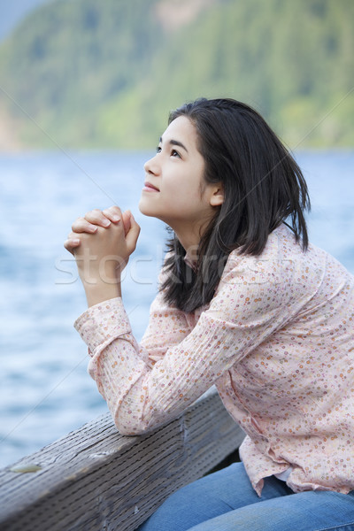 Stock photo: Young teen girl sitting quietly on lake pier, praying