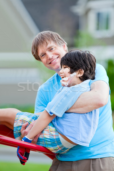 Father helping disabled seven year old son play at playground Stock photo © jarenwicklund