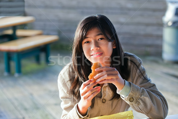 Young biracial teen girl outdoors eating hamburger Stock photo © jarenwicklund