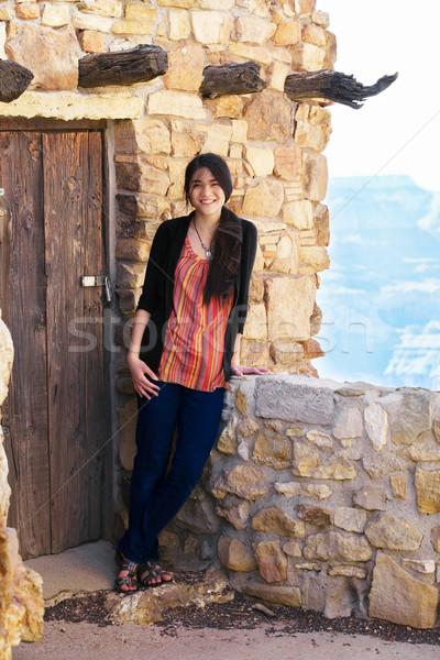 Biracial teen girl relaxing, leaning against rock wall overlooki Stock photo © jarenwicklund