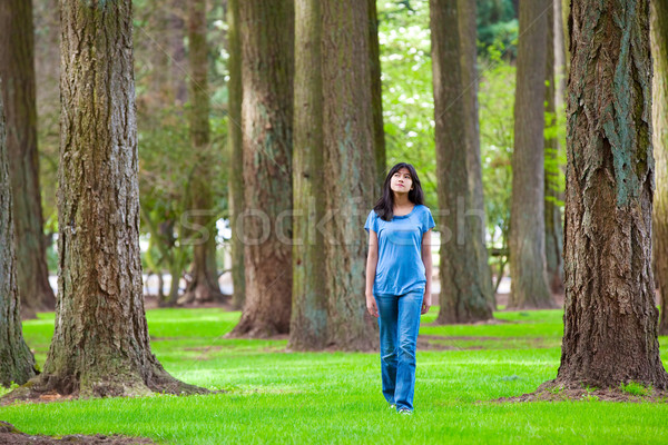 Young teen biracial girl walking under tall trees Stock photo © jarenwicklund