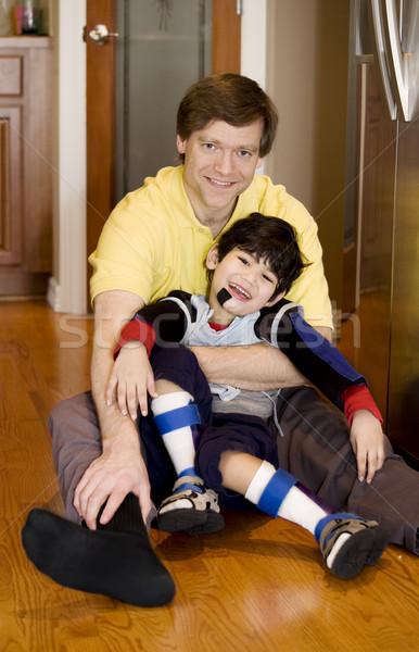 Father holding disabled son on kitchen floor Stock photo © jarenwicklund