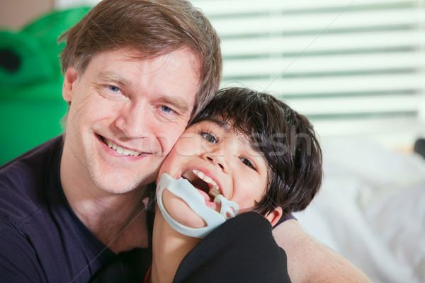 Smiling father holding disabled son Stock photo © jarenwicklund