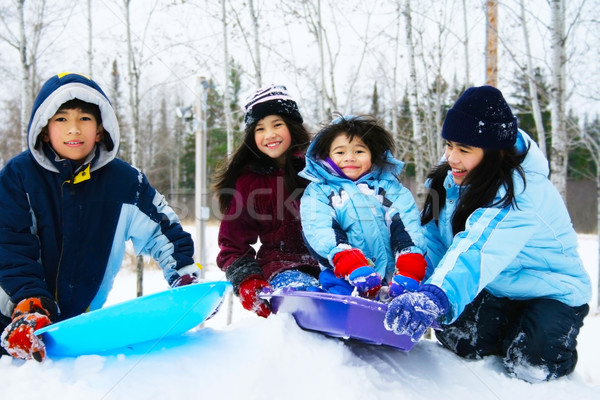 Four kids enjoying winter outdoors on a sled on snow covered hil Stock photo © jarenwicklund