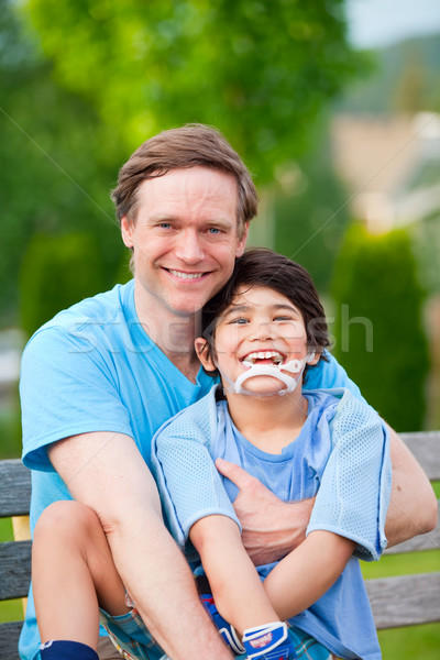Handsome father holding smiling disabled son outdoors Stock photo © jarenwicklund