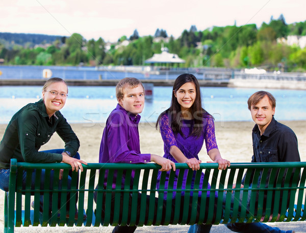 Four young multiethnic friends together at beach Stock photo © jarenwicklund