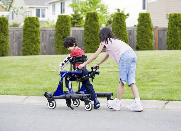 Big sister helping younger disabled brother in walker Stock photo © jarenwicklund